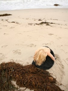jena-ardell-young-woman-wearing-a-dress-alone-on-an-empty-beach-near-the-sea